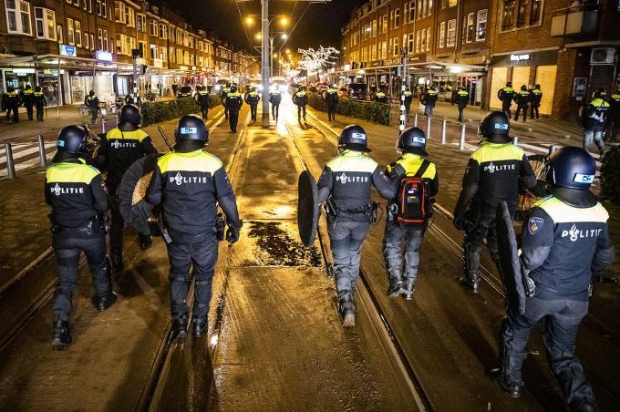 Politie in Rotterdam is massaal in de stad aanwezig na de rellen van een dag eerder en controleert mensen die in groepjes op straat lopen. ANP