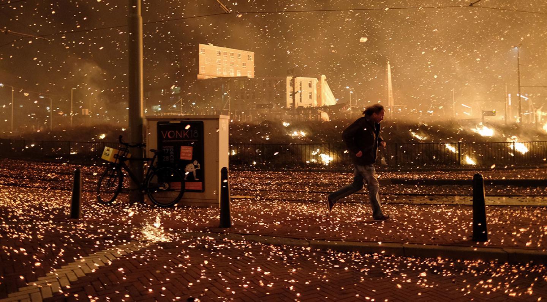 Scheveningen, 1 januari 2019 - De vonken van het vreugdevuur waaien de verkeerde kant op, wat voor schade en brandgevaar zorgt. Foto: Eric Brinkhorst